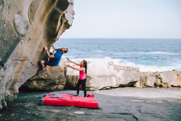 Foto op Aluminium Alpinisme Young couple rock climbing cliffs at the coast helping eachother