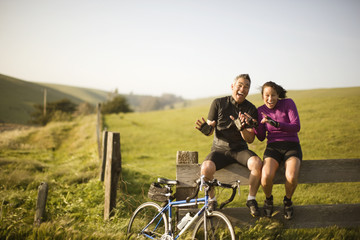 Male and female cyclists sitting on a fence waving their hands and laughing