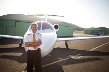 Pilot standing in front of a private jet and smiling