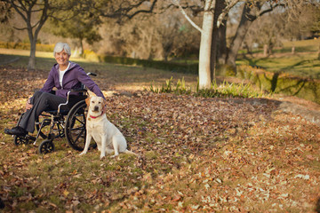 Portrait of a smiling senior woman sitting in a wheelchair next to her dog in a park.