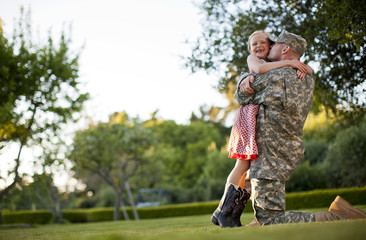 Male soldier hugging his young daughter in the back yard of their home.