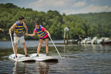 Young couple playfully flirting on paddleboards.
