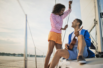 Happy young couple having fun playing the ukulele while sailing.