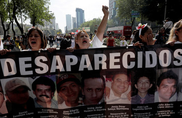 Mothers and relatives hold pictures of missing people as they march, in Mexico City