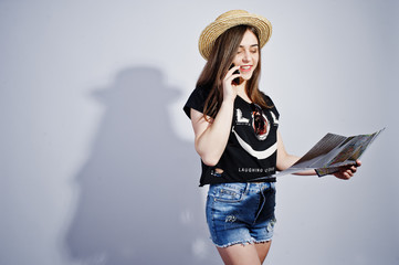 Girl tourist with map, wear in lol shirt, shorts and hat speaking on mobile phone isolated on white.