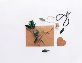Kraft envelope invitation. Letter with olive branch over white background. Flat lay, top view