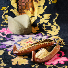 Opanci, leather folk shoes, a part of the Serbian national costume, are lying on a kilim, a traditional handmade flat-woven floor rug. A Serbian folk cap (a shajkacha) is in a blurry background.