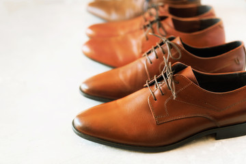 Different models and brown colors of shoes on gay background. Selective focus. Sale and shopping concept. Copy space. Banner. Classic fashion polished men's brown shoes.