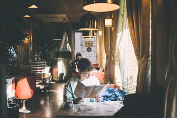 喫茶店でメニューを見る女性