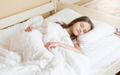 Portrait of cute girl with long hair sleeping in bed