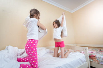 Two beautiful girls fighting with pillows on bed at bedroom
