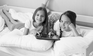 Black and white portrait of two sisters lying in bedroom and using digital tablet