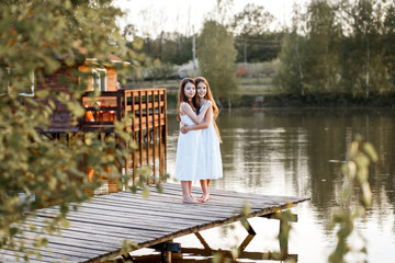Beautiful girls friends with long brunette hair ans blue eyes having fun on the pier with beautiful wiev near the water at the sunset