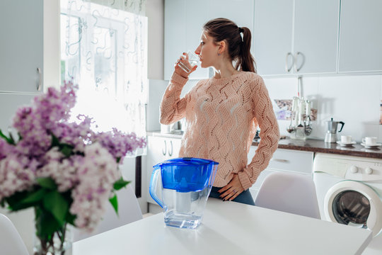 Woman drinking filtered water from filter jug in kitchen. Modern kitchen design. Healthy lifestyle