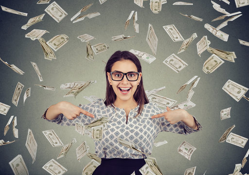 excited woman pointing fingers at herself in disbelief of being a winner under a money rain