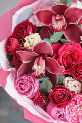 Bright red bouquet of beautiful flowers on wooden table. Floristry concept. Spring colors. the work of the florist at a flower shop. Vertical photo