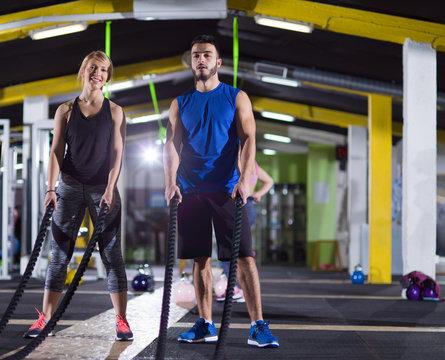 sports couple doing battle ropes crossfitness exercise