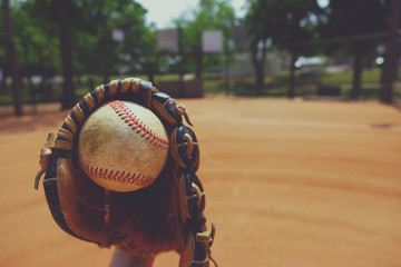 Old used baseball caught in glove, nostalgia of the sport with ball field in background.