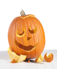 Halloween Pumpkin being carved with pieces and knife on a Wood Board Table and against a white background.   Vertical crop