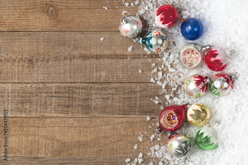 christmas ornaments in snow on side of rustic weathered and