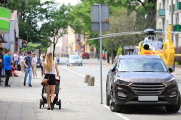 Fototapeta Piękna kobieta, blondynka idzie z wózkiem obok śmigłowca ratunkowego w Opolu. obraz