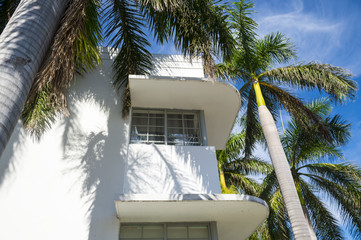 Detail of typical Art Deco architecture with palm trees and blue sky in South Beach, Miami, Florida