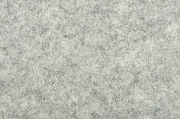 Gray felt surface. Textile material, made of matted synthetic fibers. White, gray and black acrylic pressed together. Fabric pattern. Background. Photography from above.