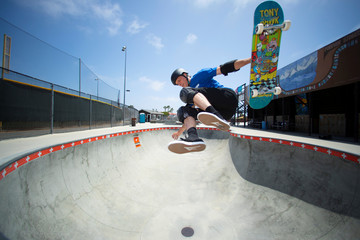 Two days before his 50th birthday professional skateboarder Tony Hawk pulls out of an aerial  maneuver in a pool during a photo session at the YMCA Skatepark in Encinitas, California