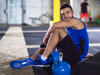 young athlete man sitting on the floor and relaxing