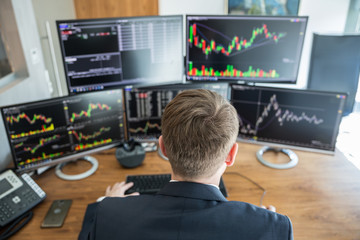Over the shoulder view of businessman trading stocks. Stock traders looking at graphs, indexes, numbers and analyses on multiple computer screens in modern trading office.