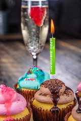 Several cupcakes on a wooden cutting board with a birthday single candle and glass of Champagne