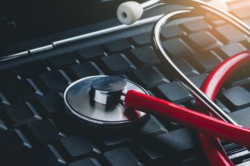 stethoscope on keyboard laptop computer