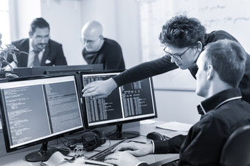 Startup business and entrepreneurship problem solving. Young AI programmers and IT software developers team brainstorming and programming on desktop computer in startup company. Greyscale blue toned.