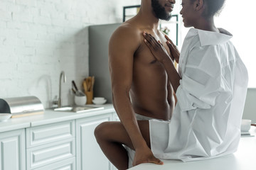 cropped image of african american lovers in morning at kitchen