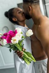 african american couple kissing and girlfriend holding bouquet of flowers at kitchen