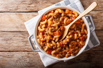 american chop suey, american goulash, with elbow pasta, beef and tomatoes close-up. Horizontal top view