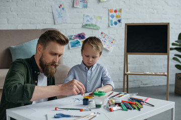 focused father and cute little son with paints and brushes drawing pictures together at home