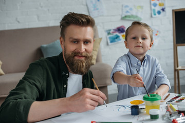 smiling father and cute little son with paints and brushes looking at camera together at home