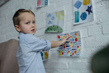 little kid looking at camera while hanging childish pictures on wall at home