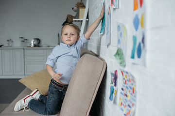 side view of little kid hanging childish pictures on wall at home
