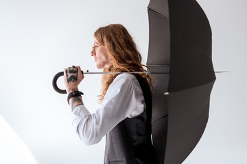 side view of stylish tattooed businessman with curly hair holding black umbrella