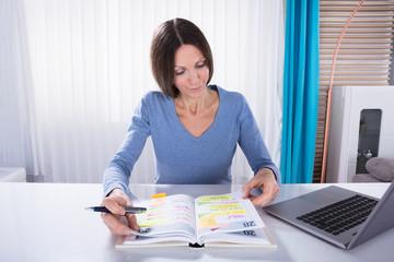 Fototapete - Woman Looking At Calendar Diary
