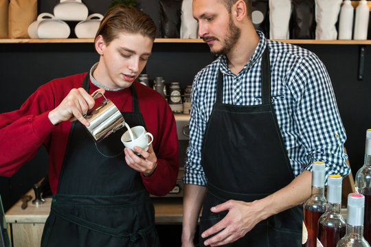 first or part time or summer job concept. professional barista teaching young man how to prepare cappuccino or latte.