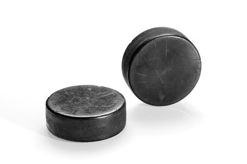 Two hockey pucks on a white background