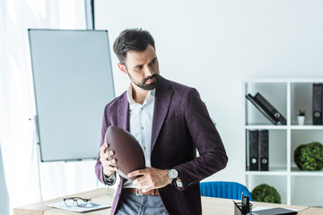 handsome young businessman with american football ball at office