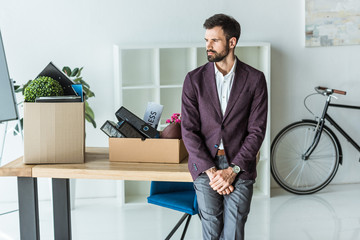 thoughtful young businessman with boxes of personal stuff leaning back on desk at office