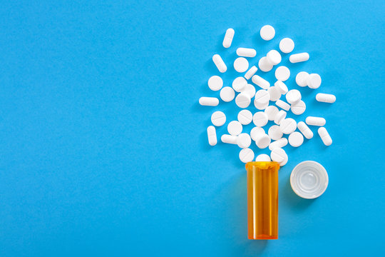 Medicine, opioid painkillers and prescription medicines concept with top view of orange prescription bottle of oxycodone and hydrocodone pills spilled on a blue background with copy space