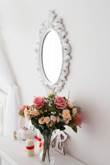 mirror with a bouquet of flowers in a white interior