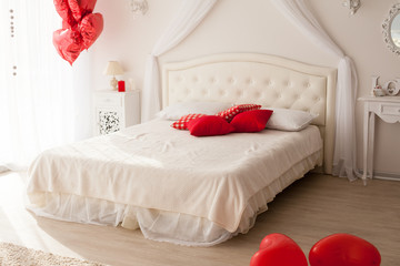 White bedroom with red balloons in the shape of a heart