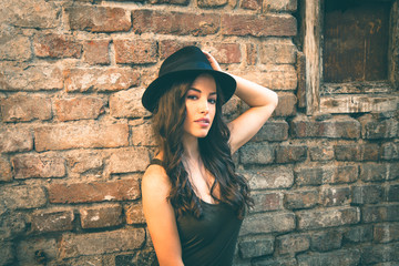 Young fashion woman with hat stand in front old abandoned house summer day